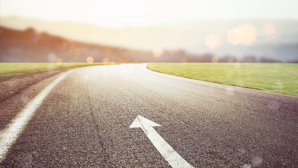 Straße mit Pfeil, der geradeaus zeigt.