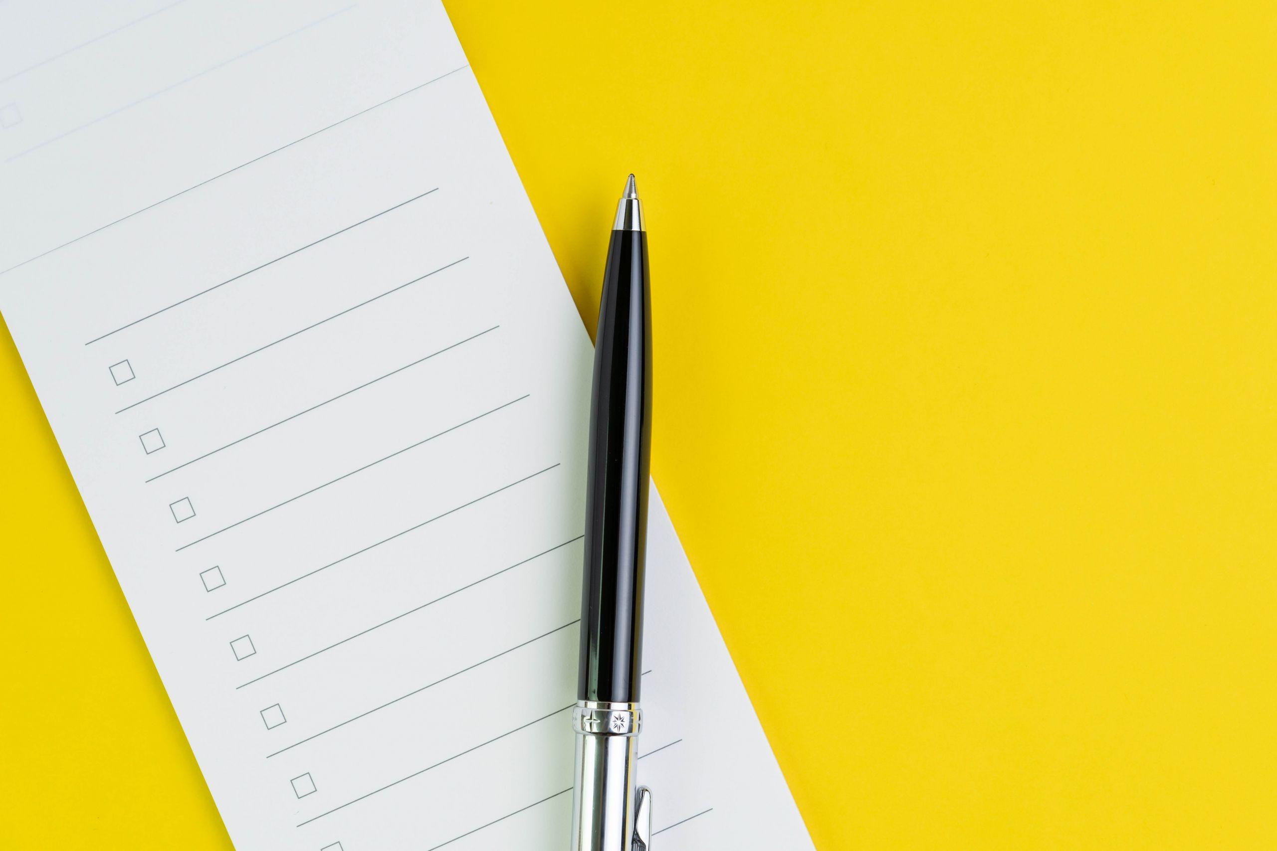 Checkliste auf gelbem Hintergrund. Auf der Checkliste liegt ein Kugelschreiber.