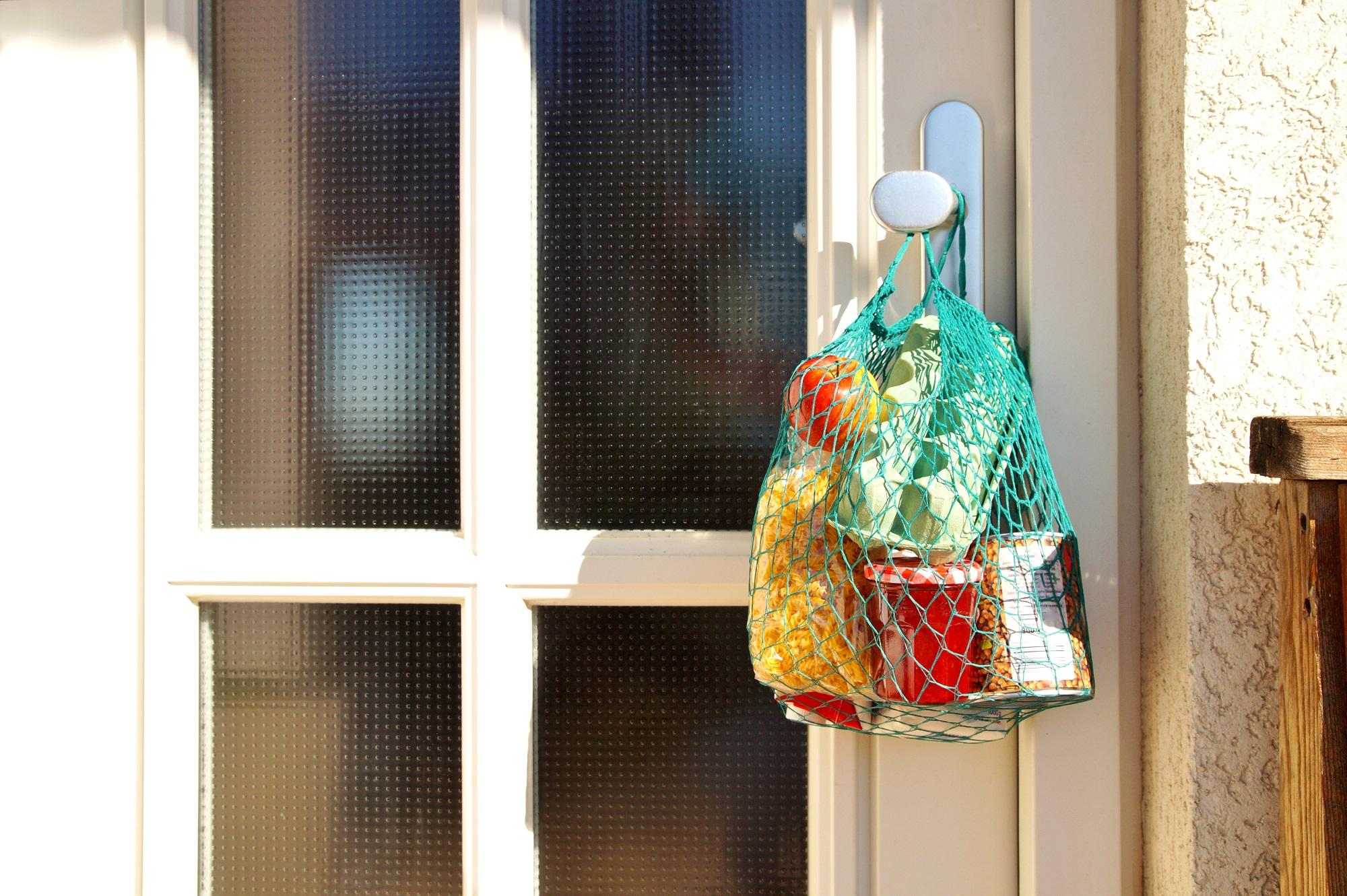 Ein mit Lebensmitteln gefüllter Stoffbeutel hängt an der Türklinke eines Wohnhauses.