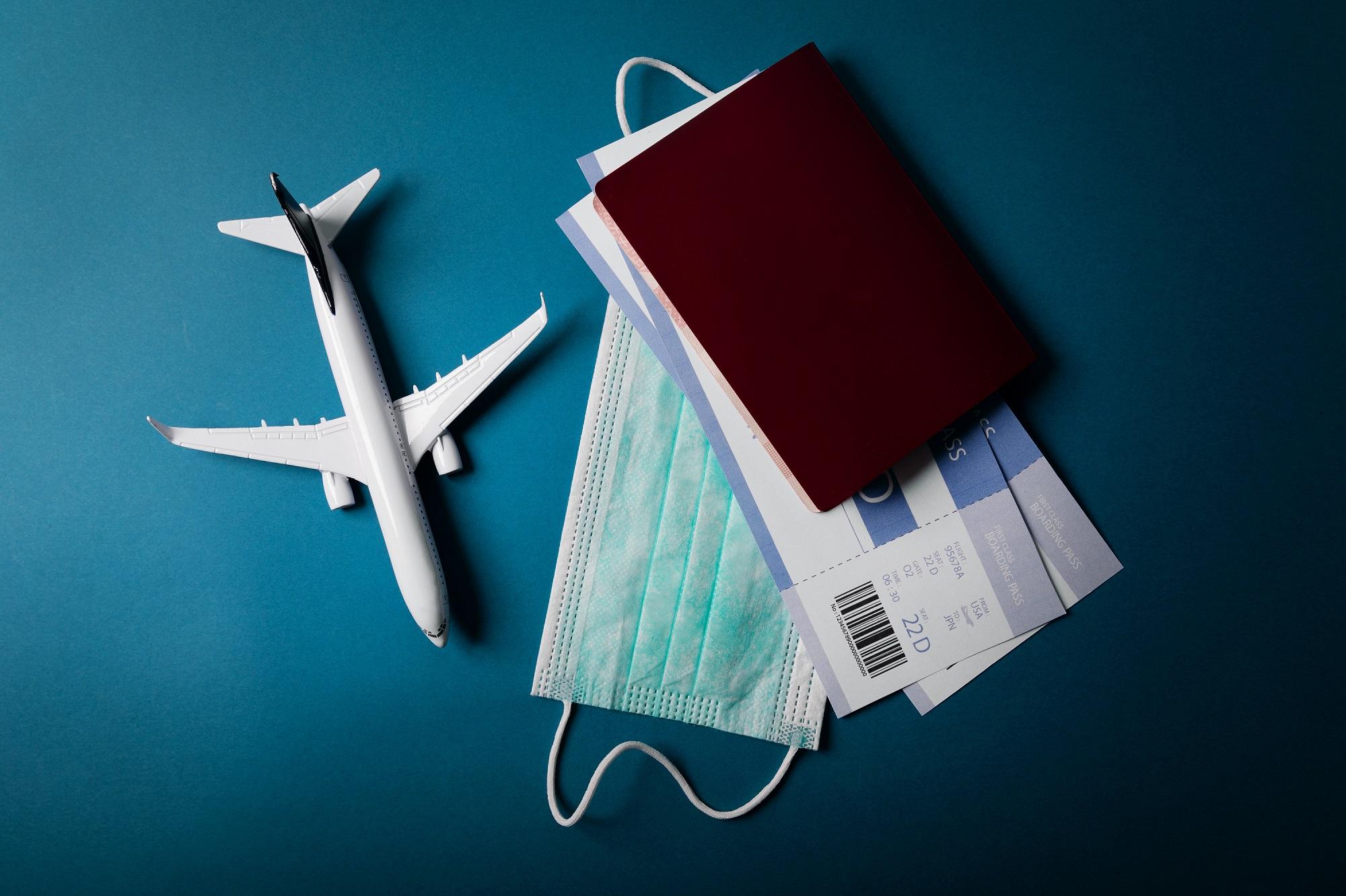 Zu sehen ist ein Miniaturflugzeug, welches neben einem Reisepass, zwei Flugtickets und einem Mund-Nasen-Schutz liegt.