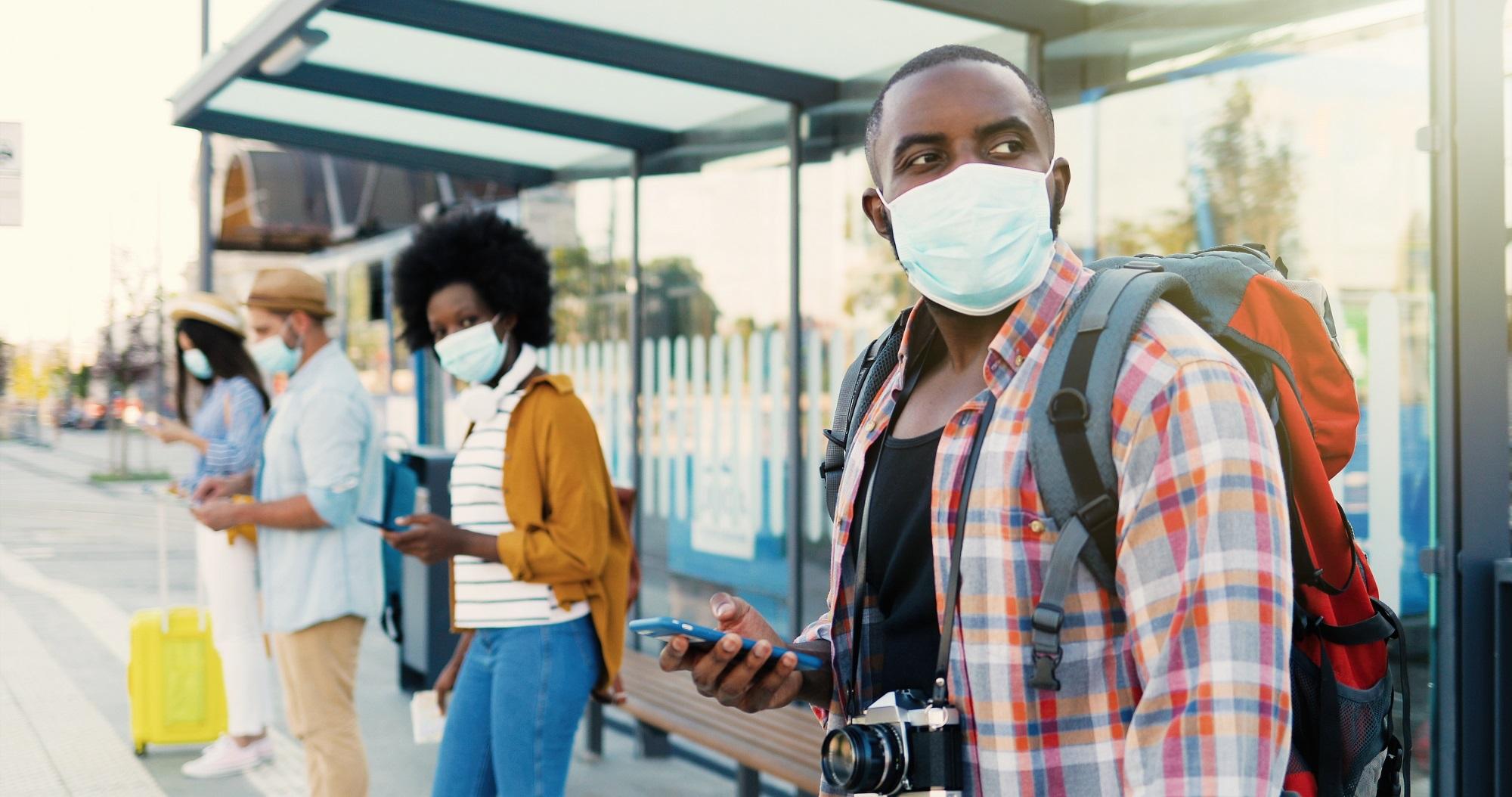 Vier Personen warten an einer Bushaltestelle und tragen einen Mund-Nasen-Schutz.